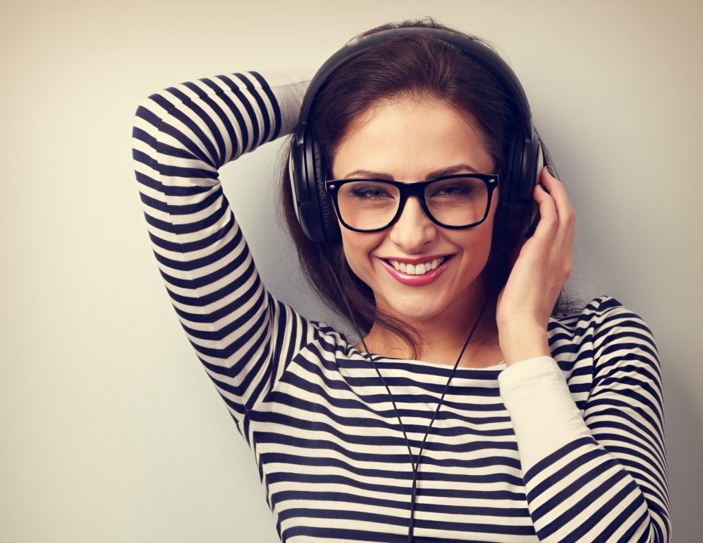 Happy smiling young woman listening music wearing the headphones. VIntage closeup portrait